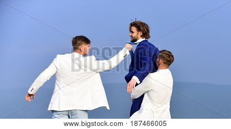 Young People Fighting In Nature On Blue Sky Background
