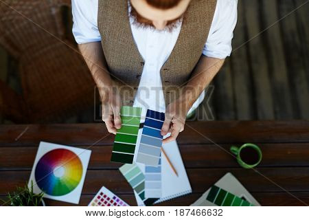 Directly above view portrait of creative man working in modern design studio, choosing color scheme from swatches