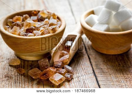 lumps of white and brown sugar on wooden kitchen table background