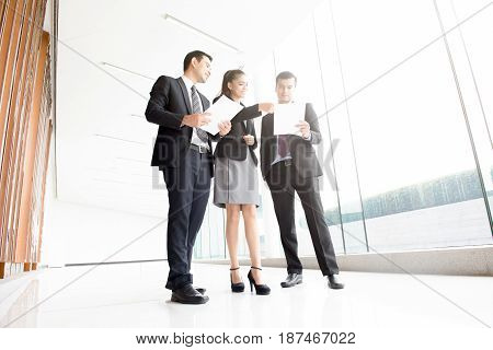 Business people discussing documents in office building hallway