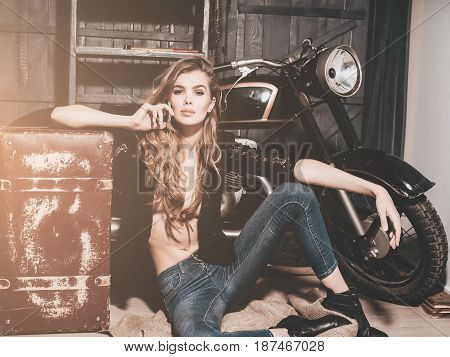 biker or pretty woman with long blond hair in erotic shirt and jeans with vintage suitcase at bike in garage with mobile phone on grey wooden background.