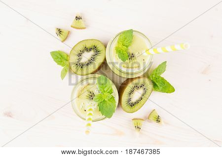 Green kiwi fruit smoothie in glass jars with straw mint leaf cut ripe berry close up top view. White wooden board background.