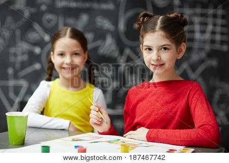 Portrait of two happy little girls looking at camera while painting together in art studio class