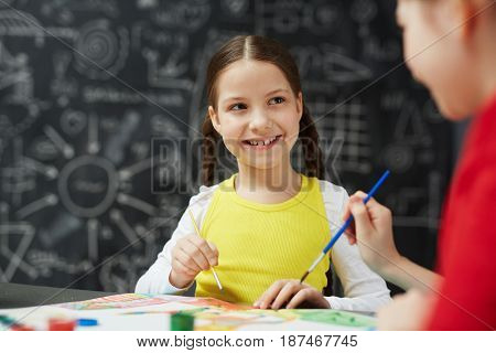 Portrait of cute smiling little girl painting pictures with friend during art lesson in school sitting against blackboard