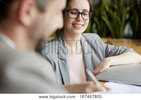 Young businesswoman signing contract with partner