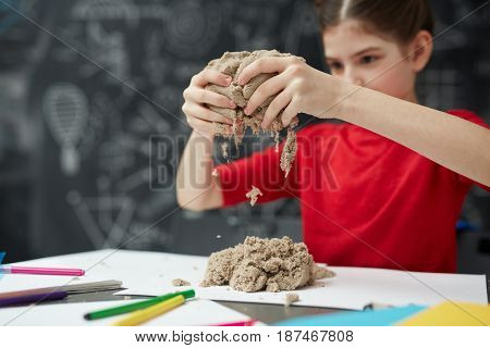 Portrait of little girl playing with kinetic sand during art class in child development center, focus on sand in hands