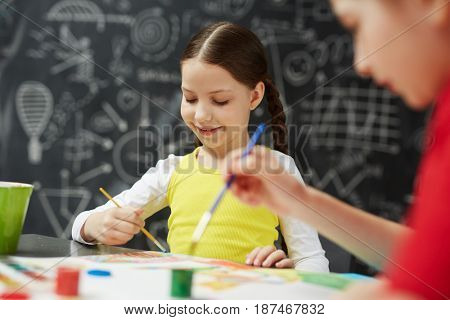 Portrait of cute smiling little children painting pictures in art studio class sitting against blackboard