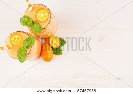 Decorative frame of orange citrus kumquat fruit smoothie in glass jars with straw mint leaf cute ripe berry top view. White wooden board background copy space.