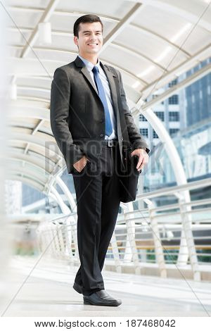 Smiling young businessman carrying bag while walking in outdoor covered walkway full body