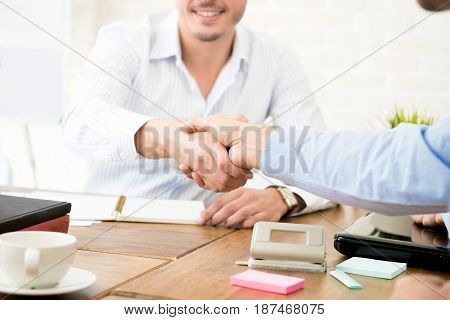 Casual businessmen making handshake at working table in the office