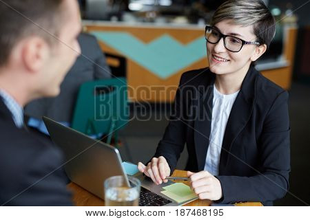 Portrait of young creative businesswoman talking to man at table while discussing work issues and smiling