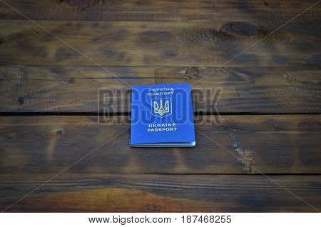 Photo Of The Ukrainian Foreign Passport, Lying On A Dark Wooden Surface. The Concept Of Introducing