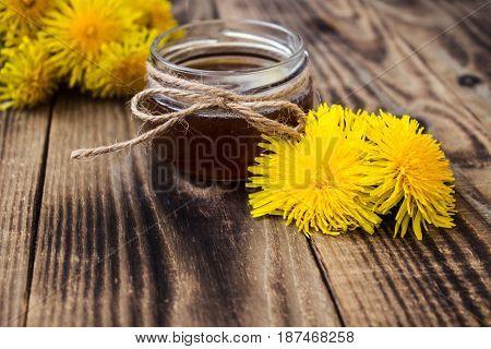 dandelion jam or honey in jar with fresh flowers on wooden background