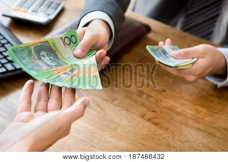 Businessman giving money (australian dollars) at working desk - loanbribery and financial concepts