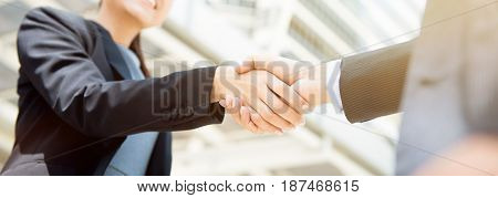Businesswoman making handshake with a businessman female leader concept - panoramic web banner