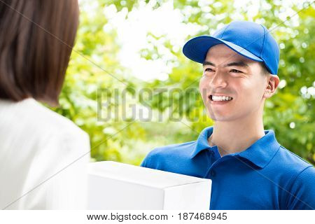 Smiling delivery man in blue uniform delivering parcel box to a woman - courier service concept