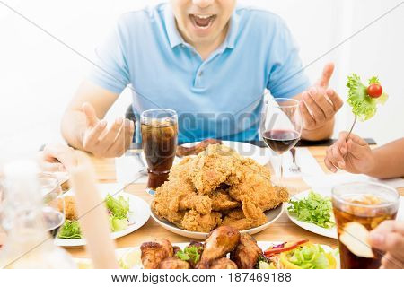 Food and drinks on dining table in front of excited hungry young man