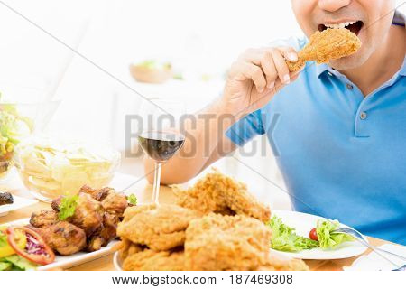 Young man eating fried chicken in the restaurant