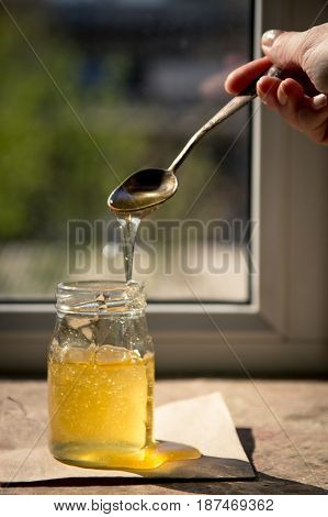 Honey Dripping From A Spoon. Organic Pure Honey In Jar