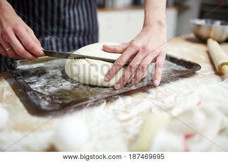 Baker kneading dough and forming loaf of bread