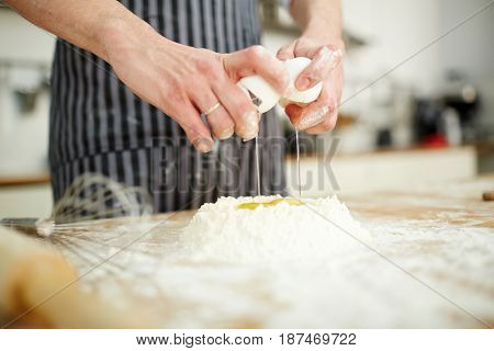 Baker breaking raw egg into wheaten flour