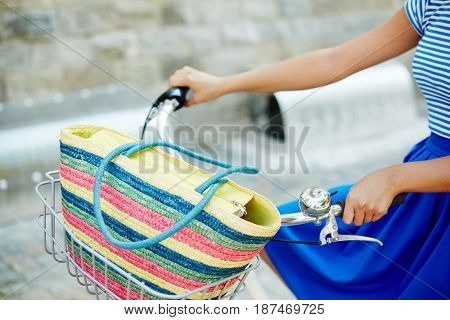 Striped bag in basket of bicycle being riden by girl