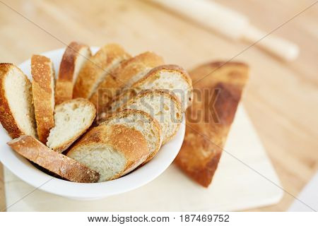 Plate with crusty bread cut into slices
