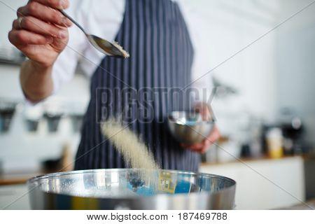 Baker adding salt in bowl with ingredients