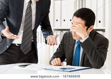 Young businessman getting stressed by his boss at the meeting in the office