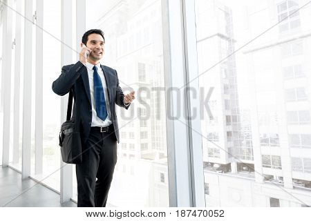 Asian businessman talking on mobile phone while walking at office building hallway