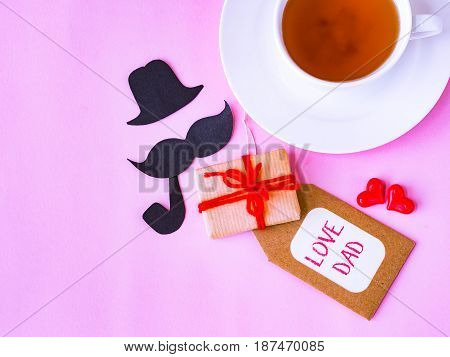 Father's day concept. LOVE DAD alphabet with gifts tea cup with black Mustache on pink background