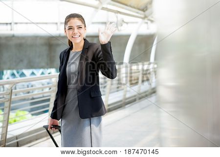 Young Asian businesswoman with baggage waving hand bye bye - business travel concept