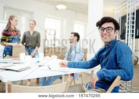 Leader of team of designers looking at camera in working environment