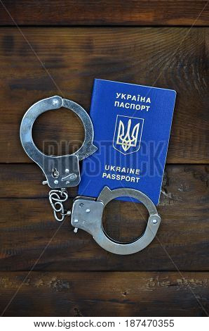 A Ukrainian Passport With Police Handcuffs Lies On A Wooden Table. Problems With The Law During The