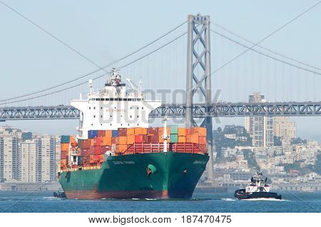 San Francisco CA - May 21 2017: Cargo ship SEASPAN CHINAN manuevering under the Bay Bridge in route to the Port of Oakland the fifth busiest port in the United States.