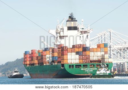 Oakland CA - May 21 2017: Multiple tugboats assist cargo ship SEASPAN CHIWAN to maneuver into the Port of Oakland.