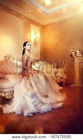 Beauty gorgeous woman in beautiful evening dress sitting and posing in Luxurious style interior room. Elegant lady full length portrait in golden dress