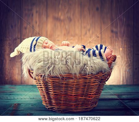 Two weeks old infant baby wearing knitted funny costume, sleeping in a basket over wooden background, studio shot. Sweet newborn baby portrait over wood rustic background.