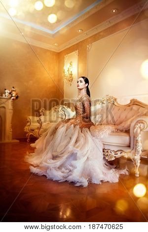 Beauty gorgeous woman in beautiful evening dress sitting and posing in Luxurious style interior room. Elegant glamour lady full length portrait in golden dress