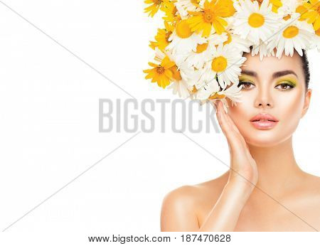 Beauty Girl with Daisy Flowers Hair Style touching her face skin. Beautiful Model woman with Blooming chamomile flowers on her head. Nature Hairstyle. Summer. Holiday Creative Makeup. Fashion Make up