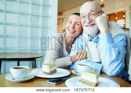 Affectionate seniors sitting in cafe