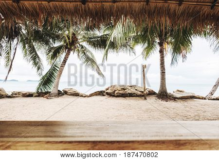 Tropical beach in summer, wood table top with blurred coconut trees, sand and the beach background