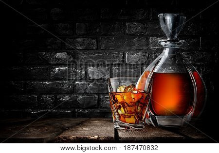 Whiskey on a wooden table in cellar with black brick wall