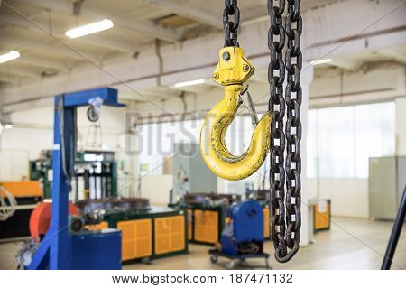 Steel load-lifting hook. Black steel chain. Industrial shop.