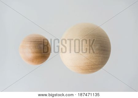 Surreal design concept - real wooden ball float on grey background like the planet on the universe