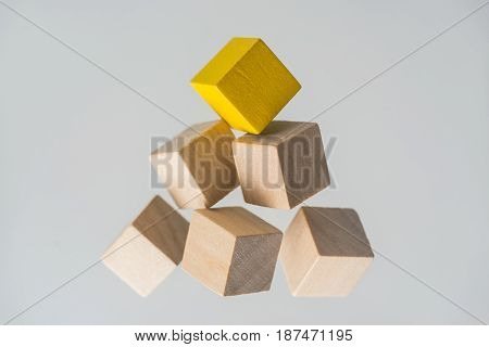 Business concept - Abstract geometric real floating wooden cubes layout like triangle on grey background and it's not 3D render. the symbol of leadership teamwork and growth.
