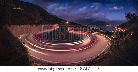 Winding road in the Montenegro valley at night. The light path headlights of cars. Adriatic sea with mountains on a skyline.