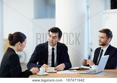 Young specialist answering questions of two employers during interview