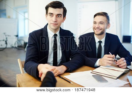 Happy leader handshaking with new partner or employee