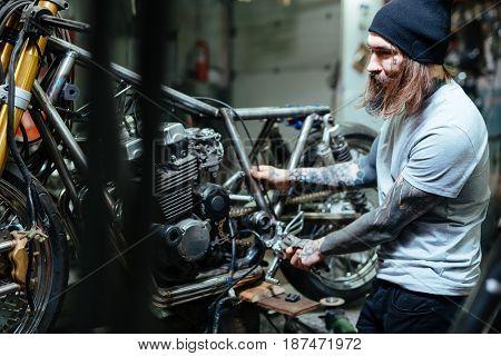 Hipster with tattoos repairing broken bikes